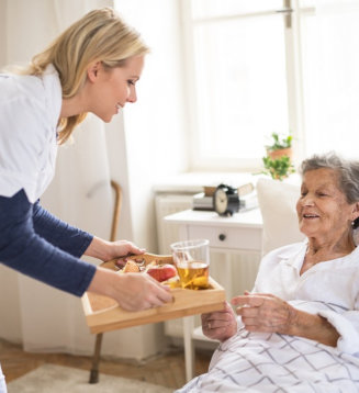 caregiver serving food to her senior patient