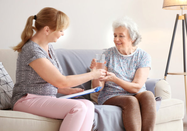caregiver giving her senior patient a glass of water