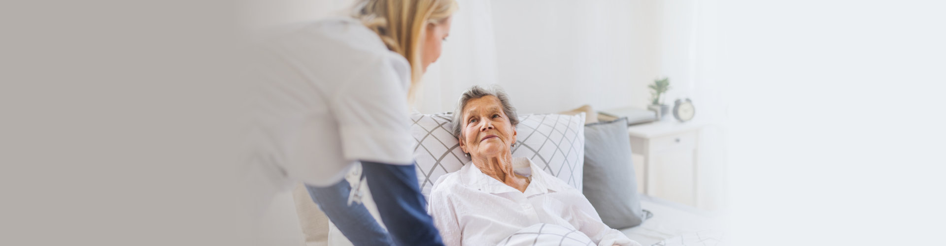 senior woman in bed and her caregiver